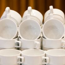 White cups for tea piled on table for coffee-break